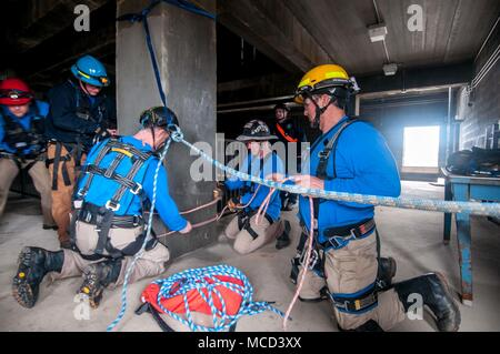 Firefighters from the Mississippi Task Force, Urban Search and Rescue team secure a system of ropes to enable their teammate's escape from a simulated collapsed building during the training exercise PATRIOT South 18, at Camp Shelby, Miss. on Feb. 14, 2018. PATRIOT South, a joint-agency domestic operations training exercise, focuses on natural disaster preparedness for not only National Guard units from across the nation, but also civilian first responders. (Ohio Air National Guard photo by Tech. Sgt. Nic Kuetemeyer) - Stock Photo