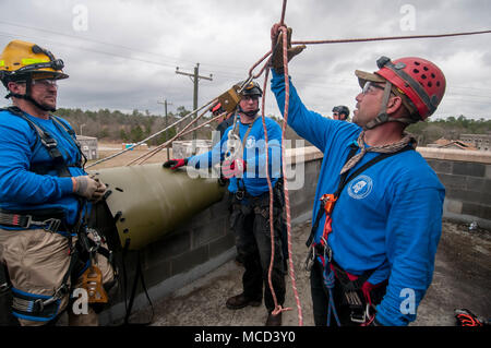 Firefighters from the Mississippi Task Force Urban Search and Rescue team check their knots and angles at which their ropes are stressed, before descending on pulleys and harnesses from the roof of a simulated collapsed building during the training exercise PATRIOT South 18, at Camp Shelby, Miss. on Feb. 14, 2018. PATRIOT South, a joint-agency domestic operations training exercise, focuses on natural disaster preparedness for not only National Guard units from across the nation, but also civilian first responders. (Ohio Air National Guard photo by Tech. Sgt. Nic Kuetemeyer) - Stock Photo