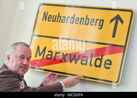 10 April 2018, Germany, Neuhardenberg: Dietmar Zimmermann, chairman of the local heritage association 'Heimatverein Neuhardenberg e.V.' places a road sign which reads 'Neuhardenberg - Marxwalde' on a wall of the local heritage museum. The town was previoulsy known as Marxwalde after German philosopher, economist and social theorist Karl Marx (May, 05 1818 - March, 14 1883) during the GDR era and renamed to Neuhardenberg after the fall of the Berlin Wall. Photo: Patrick Pleul/dpa-Zentralbild/dpa