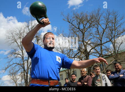 Russia. 15th Apr, 2018. CHECHNYA, RUSSIA - APRIL 15, 2018: A man takes part in a kettlebell lifting contest as part of the first Republican Cossack Games held by the Terek Cossacks community in the village of Novoshchedrinskaya, Shelkovskoi District. The Chechen Republic's Terek and Sunzha Cossack community comprises six Cossack communities in Naursky and Shelkovskoi Districts. Yelena Afonina/TASS Credit: ITAR-TASS News Agency/Alamy Live News - Stock Photo