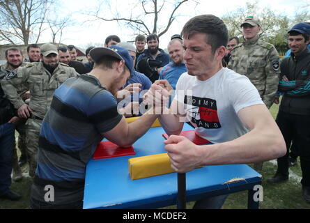 Russia. 15th Apr, 2018. CHECHNYA, RUSSIA - APRIL 15, 2018: Men compete in an arm wrestling contest as part of the first Republican Cossack Games held by the Terek Cossacks community in the village of Novoshchedrinskaya, Shelkovskoi District. The Chechen Republic's Terek and Sunzha Cossack community comprises six Cossack communities in Naursky and Shelkovskoi Districts. Yelena Afonina/TASS Credit: ITAR-TASS News Agency/Alamy Live News - Stock Photo