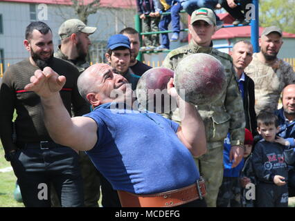 Russia. 15th Apr, 2018. CHECHNYA, RUSSIA - APRIL 15, 2018: A man lifts a dumbbell during the first Republican Cossack Games held by the Terek Cossacks community in the village of Novoshchedrinskaya, Shelkovskoi District. The Chechen Republic's Terek and Sunzha Cossack community comprises six Cossack communities in Naursky and Shelkovskoi Districts. Yelena Afonina/TASS Credit: ITAR-TASS News Agency/Alamy Live News - Stock Photo