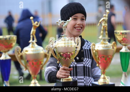 Russia. 15th Apr, 2018. CHECHNYA, RUSSIA - APRIL 15, 2018: A boy holds trophies for winners of the first Republican Cossack Games held by the Terek Cossacks community in the village of Novoshchedrinskaya, Shelkovskoi District. The Chechen Republic's Terek and Sunzha Cossack community comprises six Cossack communities in Naursky and Shelkovskoi Districts. Yelena Afonina/TASS Credit: ITAR-TASS News Agency/Alamy Live News - Stock Photo