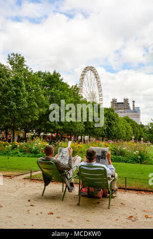 A couple reading the newspaper at the Tuellieries gardens of the Louvre in Paris. - Stock Photo