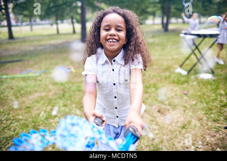 African American Girl Making Soap Bubbles - Stock Photo