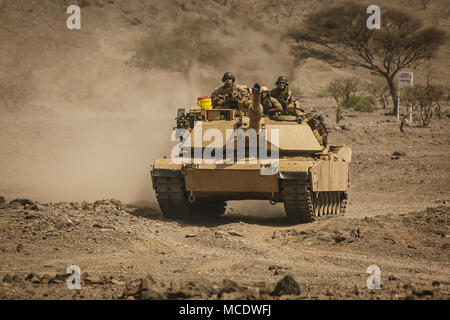 U.S. 5TH FLEET AREA OF OPERATIONS (April 3, 2018) U.S. Marines assigned to Tank Platoon, Fox Company, Battalion Landing Team, 2nd Battalion, 6th Marine Regiment, 26th Marine Expeditionary Unit (MEU), drive a M1A1 Abrams tank, attached to the same unit, to a live-fire range. The 26th MEU trains to sustain expeditionary readiness across a range of critical capabilities both afloat and ashore in order to be prepared to respond to crisis in the U.S. 5th Fleet Area of Operations. (U.S. Marine Corps photo by Staff Sgt. Dengrier M. Baez/Released) - Stock Photo