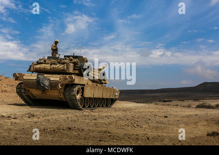 U.S. 5TH FLEET AREA OF OPERATIONS (April 3, 2018) U.S. Marines assigned to Tank Platoon, Fox Company, Battalion Landing Team, 2nd Battalion, 6th Marine Regiment, 26th Marine Expeditionary Unit (MEU), and M1A1 Abrams tank, attached to the same unit, stage for a live-fire range. The 26th MEU trains to sustain expeditionary readiness across a range of critical capabilities both afloat and ashore in order to be prepared to respond to crisis in the U.S. 5th Fleet Area of Operations. (U.S. Marine Corps photo by Staff Sgt. Dengrier M. Baez/Released) - Stock Photo