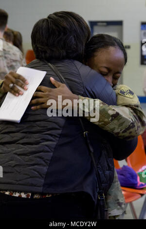 A Maryland National Guard soldier, 629th Expeditionary Military Intelligence Battalion, says goodbye before departing for a deployment to Ft. Gordon, Georgia from Laurel, Maryland on Feb. 26, 2018. Ten military intelligence soldiers from the Maryland National Guard will support the active duty command through performing geospatial intelligence imagery; analyzing overhead and aerial imagery from photographic and electronic capabilities. (U.S. National Guard photo by Cpl. Elizabeth Scott) - Stock Photo