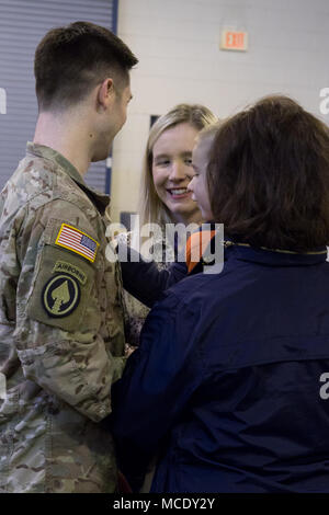A Maryland National Guard soldier, 629th Expeditionary Military Intelligence Battalion, talks to family before departing for a deployment to Ft. Gordon, Georgia from Laurel, Maryland on Feb. 26, 2018. Ten military intelligence soldiers from the Maryland National Guard will support the active duty command through performing geospatial intelligence imagery; analyzing overhead and aerial imagery from photographic and electronic capabilities. (U.S. National Guard photo by Cpl. Elizabeth Scott) - Stock Photo