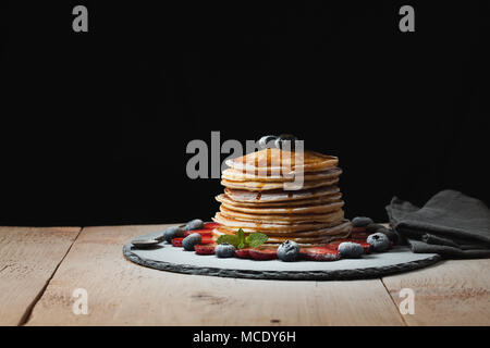 Front view of Stack of homemade plain pancakes with strawberries, blueberries and maple syrup served on black plate on black background with selective - Stock Photo
