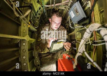 Senior Airman Kaiden Stanley, 723d Aircraft Maintenance Squadron integrated flight control systems specialist, reads a technical order while inside the transition section of an HH-60G Pavehawk, Feb. 27, 2018, at Moody Air Force Base, Ga. They were evaluated on their ability to unfold the tail and main rotors of a Pavehawk to practice making the helicopter operational in a limited amount of time. (U.S. Air Force photo by Airman Eugene Oliver) - Stock Photo