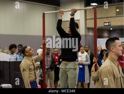 Corporal Jorge Rosales, a Marketing and Communication Marine with 6th Marine Corps District, observes an attendant of the Central Intercollegiate Athletic Association (CIAA) Education Day doing pullups at the Charlotte Convention, Charlotte, North Carolina, Center on Feb. 28, 2018. The Marines took part in the Education Day at the CIAA to spread awareness and inform others of the opportunities the Marine Corps can provide. The Education Day assists recruiters by offering them different tools to reach students across the state. (U.S. Marine Corps photo by Lance Cpl. Jack A. E. Rigsby) - Stock Photo