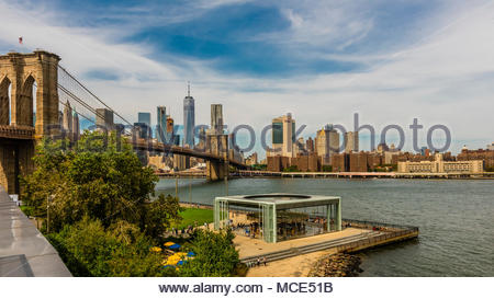 Panoramic view from DUMBO (Down Under the Manhattan Bridge Overpass) in Brooklyn across the East River to Lower Manhattan (with One World Trade Center - Stock Photo