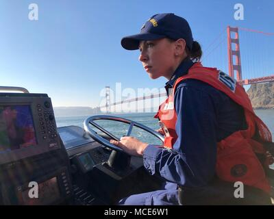 Petty Officer 1st Class Krystyna Duffy, a boatswain's mate assigned to Coast Guard Station Golden Gate in San Francisco, drives a 47-foot Motor Lifeboat near the Golden Gate Bridge, Feb. 8, 2018. In March, Duffy became the fourth active female surfman in the Coast Guard, earning the highest rank in Coast Guard boat operation and a title which dates back more than 200 years to the U.S. Life-Saving Service. (U.S. Coast Guard courtesy photo/released) - Stock Photo