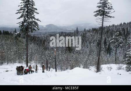Students in the Survival, Evasion, Resistance and Escape School, learn about different ways to communicate with aircraft at the Air Force Survival School Training Area in Cusick, Washington, Feb. 18, 2018. Before students go into the field for training, they have to pack a bag with specific gear to include a global positioning system, compass, map, shelter materials and rain poncho. They also pack equipment and tools used to signal for rescue. (U.S. Air Force photo/Senior Airman Sean Campbell) - Stock Photo
