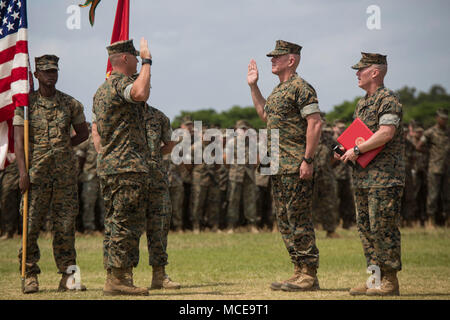Gunnery Sgt. Devin Steele re-enlists during the 3rd Marine Logistics Group 60th Anniversary celebration April 10, 2018 on Camp Hansen, Okinawa, Japan. 3rd MLG Marines and Sailors conquered numerous challenges and competed in various team competitions such as sports, fire team and squad competitions, and tug-of-war, and took part in family events and a cake-cutting ceremony. The anniversary celebration built camaraderie between the service members and families. Steele is a native of San Jose, California and Company Gunnery Sgt. for ordnance maintenance company, 3rd MLG. (U.S. Marine Corps photo - Stock Photo