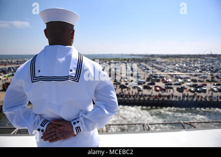 180411-N-NQ487-222  NORFOLK (April 11, 2018) Personnel Specialist 3rd Class Anthony White mans the rails aboard the aircraft carrier USS Harry S. Truman (CVN 75) during the ship's departure from homeport. Harry S. Truman is underway as the flagship for the Harry S. Truman Carrier Strike Group which includes; guided-missile cruiser USS Normandy (CG-60), and guided-missile destroyers USS Arleigh Burke (DDG-51), USS Bulkeley (DDG-84), USS Farragut (DDG-99), USS Forrest Sherman (DDG-98), USS The Sullivans (DDG-68), USS Winston S. Churchill (DDG-81) for a regularly scheduled deployment. (U.S. Navy  - Stock Photo