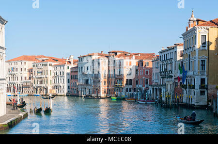 View of the famous Grand Canal in Venice, Italy. Historic Venetian canal in daylight with boats and old traditional buildings on the side - Stock Photo