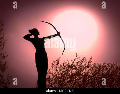 Statue of a woman Archer Silhouette with a bow target the sun - Stock Photo