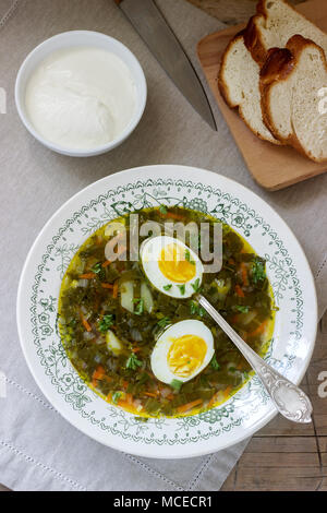Vegetarian sorrel soup with egg, served with sour cream and bread. Rustic style. - Stock Photo