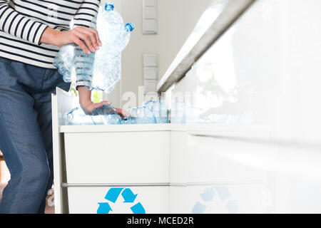 Woman caring for environment and segregating plastic bottles at home - Stock Photo