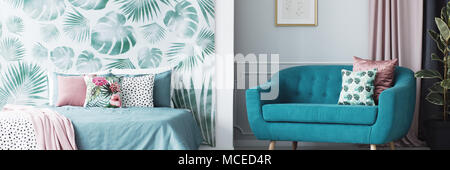 Header of an open space living room and bedroom interior with floral cushions and leaves pattern wallpaper - Stock Photo