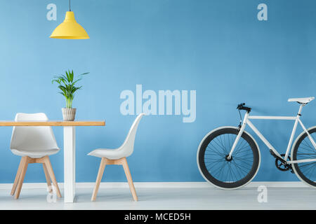 Minimal, modern interior with two chairs, a bicycle, a table with a plant on it and a yellow lamp above, against blue wall - Stock Photo