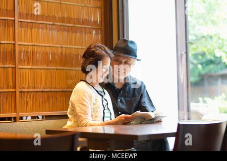 Senior couple reading books - Stock Photo