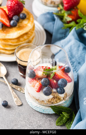 Breakfast with granola, pancakes and berries - Stock Photo