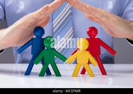 Close-up Of A Human Hand Protecting Multi Colored Human Figures On White Desk - Stock Photo