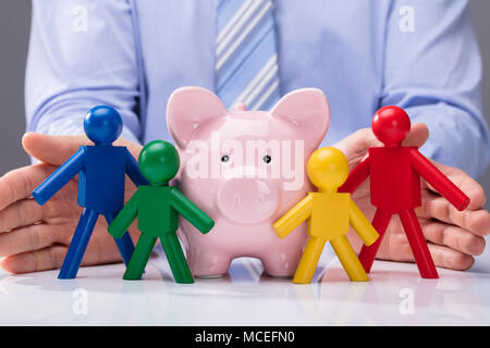 Close-up Of A Person's Hand Protecting Piggybank And Multi Colored Human Figures - Stock Photo