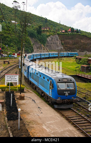 Vertical view of a diesel train arriving at Nanu-oya Train Station in the highlands of Sri Lanka. - Stock Photo