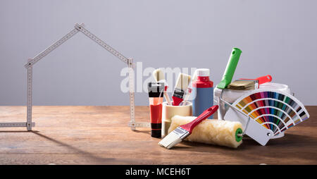 Measuring House Tape With Different Painting Equipments On The Wooden Table Against The Gray Background - Stock Photo