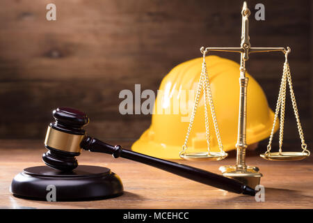 Judge Gavel In Front Of Yellow Safety Helmet And Golden Scale On The Wooden Table - Stock Photo