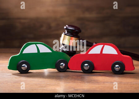 Collision Of Wooden Two Toy Cars In Front Of Gavel On The Wooden Table - Stock Photo