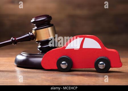 Wooden Toy Red Car In Front Of Judge Gavel On The Wooden Table Background - Stock Photo