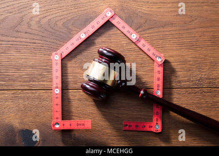 House Made With Red Measuring Tape In Front Of Wooden Judge Gavel - Stock Photo