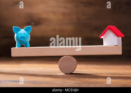 Balancing Of Blue Piggybank And Miniature House Model On The Wooden Seesaw - Stock Photo