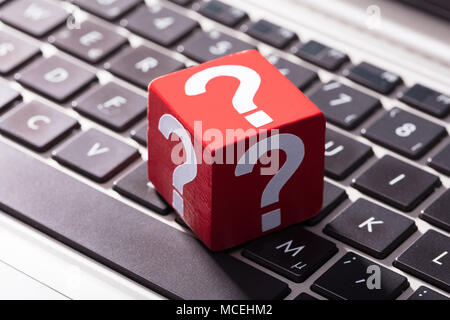 Close-up Of Question Mark Symbols On Red Block Over The Laptop Keypad - Stock Photo