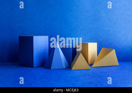 Geometrical figures still life composition. Three-dimensional blue yellow prism pyramid tetrahedron rectangular cube objects on blue background. Platonic solids figures, simplicity concept photography. - Stock Photo