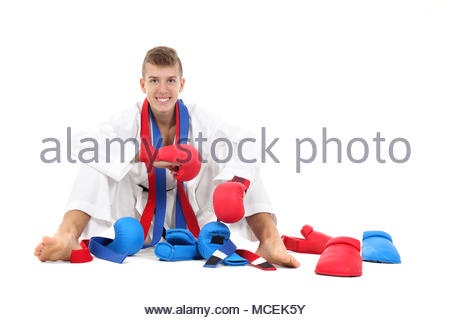 Young karate fighter in front of white background - Stock Photo