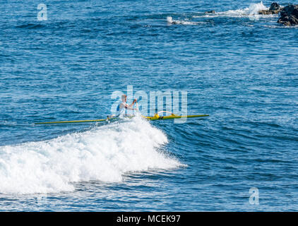 Local man paddling outrigger canoe on wave crest, Easter Island, Chile, South America - Stock Photo