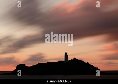 Moving clouds over Godrevy Lighthouse at Sunset - Stock Photo