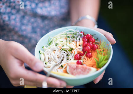 Close-up on hands holding a bowl of mixed salad. - Stock Photo