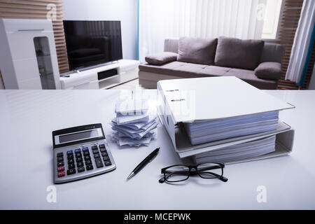Close-up Of Folders With Receipts And Calculator On White Desk In Bedroom - Stock Photo
