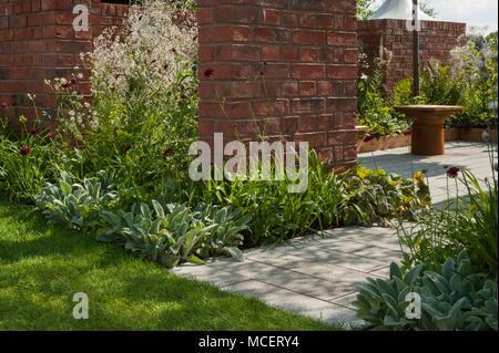 Sunny patio seating area & flowering border plants seen through gaps in walls in 'The Albert Dock Garden' - RHS Flower Show, Tatton Park, England, UK. - Stock Photo