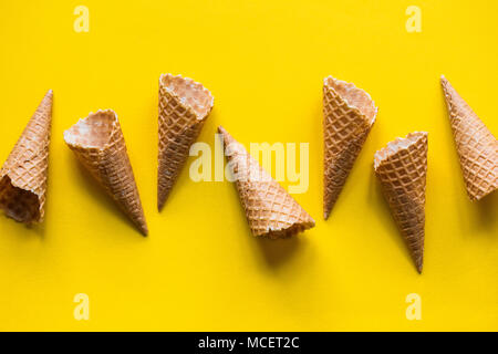 Empty waffle wafer ice cream cone on a bright yellow background - Stock Photo