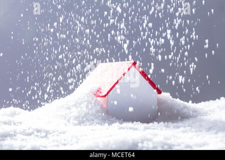 Close-up Of Snow Falling On House With Red Roof In Winter - Stock Photo