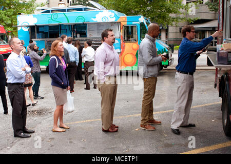 Customers wait in line to order meals from a popular food truck during their lunch hour, at 'Food Truck Thursday on October 16, 2014 in Atlanta, GA. - Stock Photo