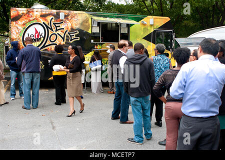 Customers stand in long line to order meals from food trucks during their lunch hour, at 'Food Truck Thursday' on October 16, 2014 in Atlanta, GA. - Stock Photo